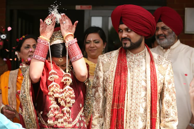 Sikh bride throwing rice over her head