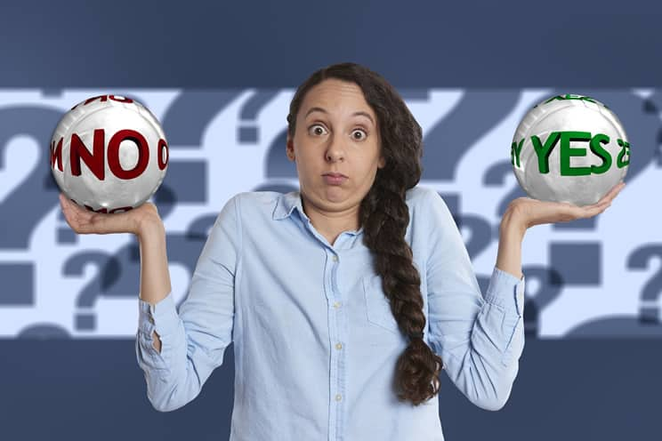 Confused woman holding up balls with yes on one ball and no on the other.