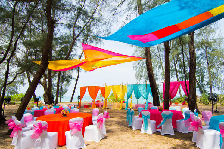 Outdoor wedding seating surrounded by colorful banners
