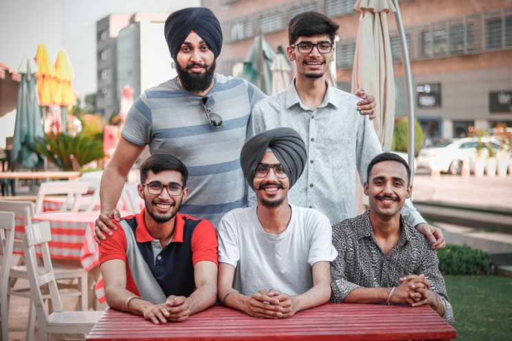 Group of Sikh men sat around table looking at the camera