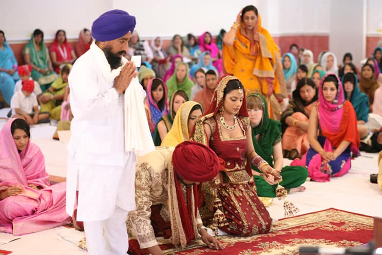 Groom wearing pagri on hands and knees in front of holy book