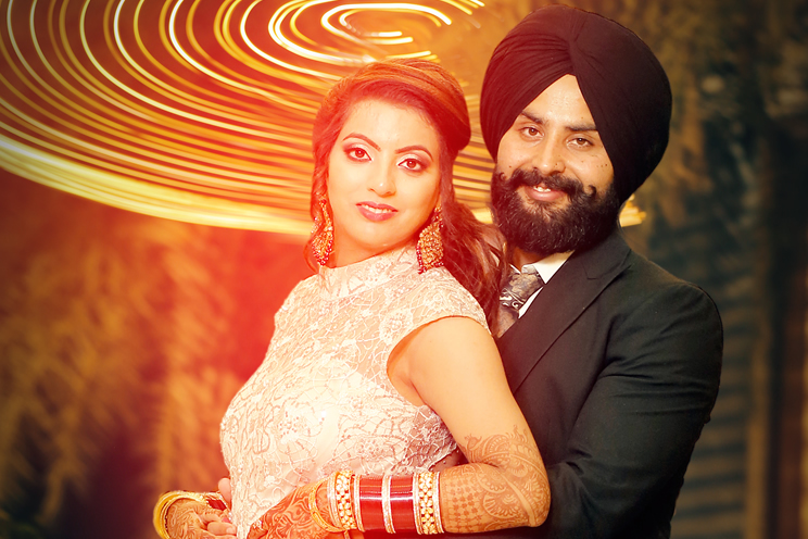 Sikh wedding couple embraced looking at camera