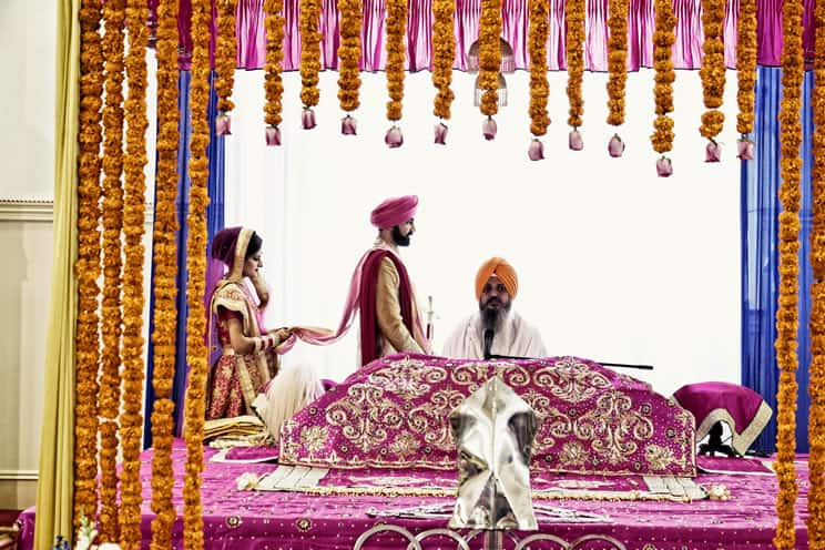 Sikh groom and bride walking around the holy book during a Sikh wedding