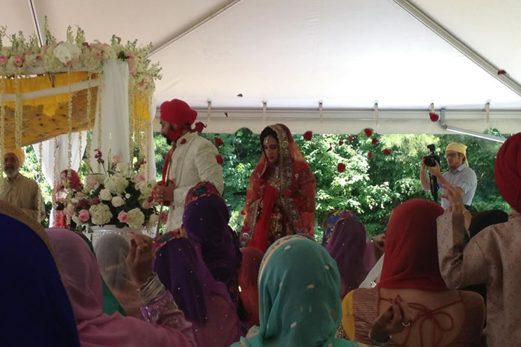 Sikh groom being followed by Sikh bride around holy book in outdoor sikh wedding.