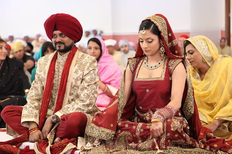 Sikh groom and bride sitting cross legged in front of the mahraj where the holy book the guru granth sahib resides